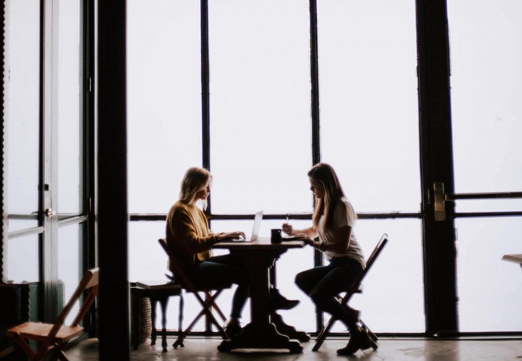 Two people talking at a table about opportunities to thrive